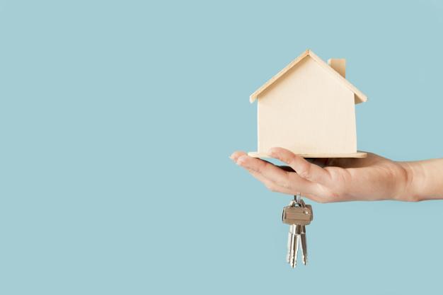 Imagem mostra pessoa segurando a casa própria nas mãos