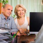Imagem mostra casal de média idade fazendo um testamento